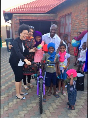 kids at Thuthuzela new home with new beanies n cycle , in pic celeste n Bafana
